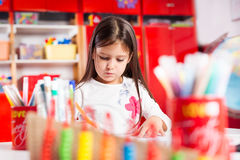 Little girl drawing on her book and having fun at play table Royalty Free Stock Photos