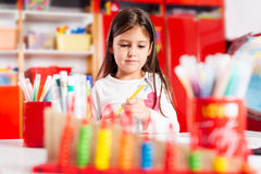 Little girl drawing on her book and having fun at play table Royalty Free Stock Image