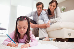 Little girl drawing with her parents in the background Royalty Free Stock Photo