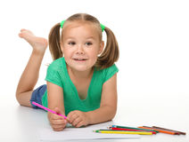 Little girl is drawing while laying on the floor Royalty Free Stock Photography