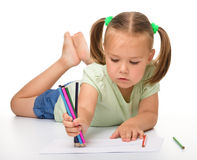 Little girl is drawing while laying on the floor Stock Images