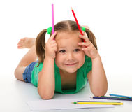 Little girl is drawing while laying on the floor Stock Photo