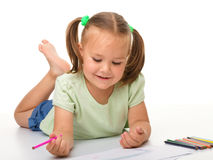 Little girl is drawing while laying on the floor Royalty Free Stock Image