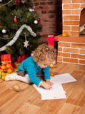 Little girl drawing near Christmas tree Royalty Free Stock Photo