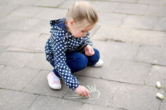 Little girl drawing outside with chalk. On cold day Royalty Free Stock Image