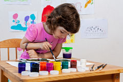 Little girl is drawing with paints and paintbrush Stock Photos
