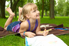 Little girl drawing. In the park on the grass Stock Image