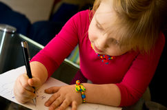 Little girl drawing with pen. A cute little girl drawing at home with a pen, focused on her children artwork stock photo