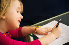 Little girl drawing with pen. A cute little girl drawing at home with a pen, focused on her children artwork royalty free stock photos