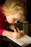 Little girl drawing with pen. A cute little girl drawing at home with a pen, focused on her children artwork stock photography