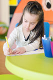 Little girl is drawing with pen Royalty Free Stock Images