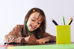 Little girl drawing with a pencil Stock Images