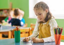 Little girl drawing with pencil in kindergarten. Royalty Free Stock Images