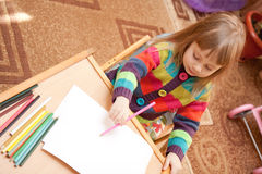 Little girl drawing with pencils at home Stock Image