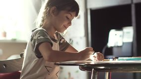 Little girl drawing with pencils at home sitting at the table. the child in the morning sun. Children draw with pencils at home sitting at a table. two little stock footage