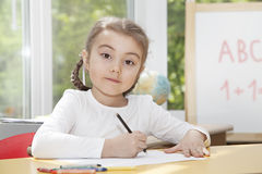 Little girl drawing with pencils Stock Images