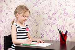 Little girl drawing with pencils at table Royalty Free Stock Images