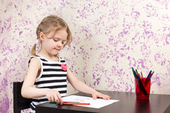 Little girl drawing with pencils at table Royalty Free Stock Photos
