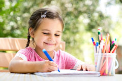 Little Girl Drawing Picture Outdoors In Summer. Little Girl Is Drawing Picture Outdoors In Summer stock image