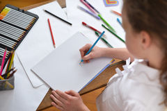 Little girl drawing picture in a sketchbook with colored pencils Royalty Free Stock Photos