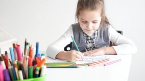 Little girl drawing a picture on white room. 7 years old girl drawing and coloring on a paper at home. stock footage