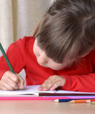 Little girl drawing and playing with a cr Royalty Free Stock Photography