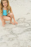 Little girl drawing in the sand Royalty Free Stock Images