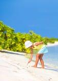 Little girl drawing on sandy beach Stock Image