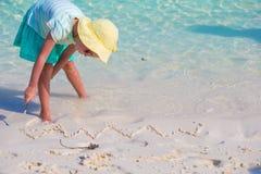 Little girl drawing on sandy beach Stock Photos