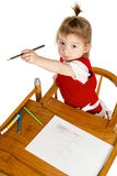 Little girl drawing showing a pencil Royalty Free Stock Image