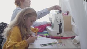 Little girl drawing sitting at the table in the foreground while her red-haired mother sews clothes near in the. Background. Seamstress works at home with her stock footage