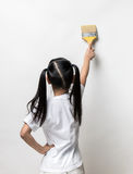 Little girl drawing something using painting brush. On wall background Stock Photography