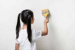Little girl drawing something using painting brush. On wall background Stock Image