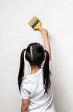 Little girl drawing something using painting brush on wall background. Royalty Free Stock Photo