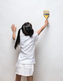 Little girl drawing something using painting brush. On wall background Royalty Free Stock Image
