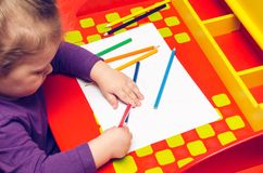A little girl is drawing something on a white sheet of paper on a red table.  Stock Photo