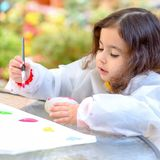 Little Girl Drawing On Stone Outdoors In Summer Sunny Day. royalty free stock photo