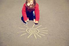 Little girl drawing sun on asphalt outdoors Stock Image