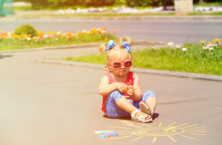 Little girl drawing sun with chalks on a street Stock Photos