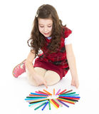 Little girl is drawing using color pencils Stock Photos