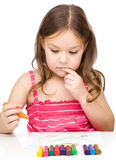 Little girl is drawing using colorful crayons royalty free stock images