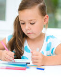 Little girl is drawing using pencils. Little girl is drawing using color pencils while sitting at table Royalty Free Stock Photography