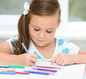 Little girl is drawing using pencils. Little girl is drawing using color pencils while sitting at table Stock Photos