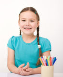 Little girl is drawing using pencils. Little girl is drawing using color pencils while sitting at table Royalty Free Stock Image
