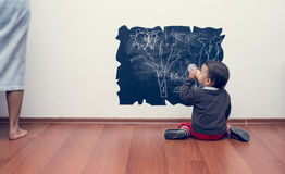 Little girl drawing on the wall. Toddler drawing on the wall and drinking milk royalty free stock photo