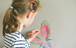 Little girl drawing on the wallpaper. Stock Photos
