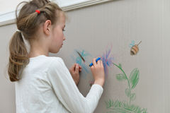 Little girl drawing on the wallpaper. Royalty Free Stock Images
