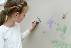 Little girl drawing on the wallpaper. Royalty Free Stock Photos