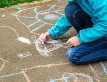 Little girl with drawings on the street Stock Image