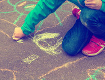 Little girl with drawings on the street. Little girl hand painting on the pavement outside, using colorful chalk, retro style Royalty Free Stock Images